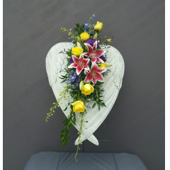 """Stunning shabby chic angel wings create a heart design with an elegant display of fresh flowers cascading through the center. This is a larger design with the heart measuring 22"""" in diameter and 32"""" tall.It is displayed on a 5ft easel for maximum visual effect. This is a metal sculpture that can be taken home and hung on a wall to create a lasting cherished memory."""