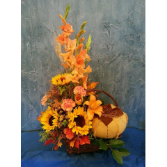 A LARGE BASKET FILLED WITH A BOUNTY OF FALL FLOWERS AND BURLAP DECORATOR PUMPKINS. THIS IS AN IMPRESSIVE BOUQUET THAT WILL BE A SHOW STOPPER WHEREVER IT IS DELIVERED. THE PLUSH PUMPKIN IS A GIFT THAT CAN BE USED SEASONALLY FOR YEARS TO COME. PERFECT FOR THE PERSON WHO HAS EVERYTHING!