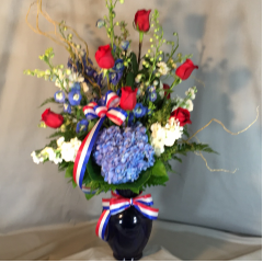 "A stunning bouquet of red roses; blue and white hybred delphinium and blue hydrangea tied off with a red/white and blue bow...Amazing!This arrangement is approximately 30"" tall and 28"" wide."