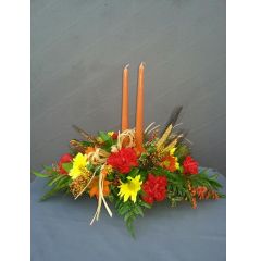 OVAL CENTERPIECE WITH A VIBRANT COLLECTION OF FALL TONE FLOWERS AND CANDLES. A TRADITIONAL CENTERPIECE TO WELCOME HOME THE FAMILY.