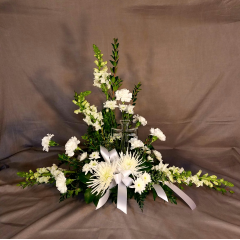 THIS IS A BEAUTIFUL TABLE TOP DESIGN WITH A KEEPSAKE 8 INCH GLASS CROSS. THIS ARRANGEMENT'S OVER ALL SIZE IS 24 INCHES TALL BY 36 INCHES WIDE.