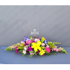 """Celebrate the Resurrection of Christ and the Easter Holiday with this beautiful spring centerpiece featuring a classic glass cross in the center of the bouquet. This arrangement will be a feature at anyone's Easter gathering. Over all length is 36"""" long."""