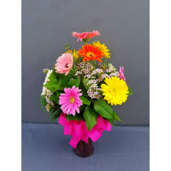 ONE DOZEN OF OUR BRIGHTEST,BOLDEST GERBERA DAISYS ARRANGED IN A TALL CYLINDRICAL VASE WITH FILLER FLOWER AND A BOW. VERY SPRINGY!