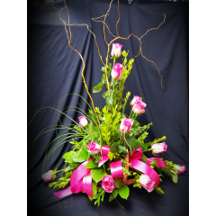 WHEN  YOU WANT MORE THAN A DOZEN ROSES, THIS BEAUTIFUL CONTEMPORARY DESIGN IS THE PERFECT CHOICE. CURLY WILLOW AND MIXED GARDEN FOLIAGE'S  TASTEFULLY ARRANGED IN A NATURAL WICKER FIRESIDE BASKET.
