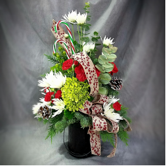 """This is a whimsical bouquet of fresh christmas greens and flowers tastefully designed in a red glass container that will make the perfect candle holder when the flowers and greens fade. It will be a container that can be used year after year to ring in the holidays! Over all height approximately 20"""" tall."""