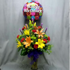 "This bouquet simply shouts happy birthday, it's your day! Yellow and orange lilies, liatris and fun button poms arranged in a vase and tied with a mylar balloon. This large arrangement is approximately 30"" tall plus the mylar balloon."