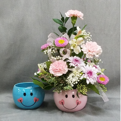 "A well crafted ceramic keepsake container overflowing with pink and lavender flowers that celebrate the birth of a very special little someone. Also available in blue tones for a precious baby boy too! approximately 15"" tall. Add a mylar balloon to finish the look!"