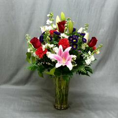 Oriental lilies are always a favorite but you can't miss when you add red roses, iris, asters and carnation in a clear cyinder vase.  Stunning bouquet