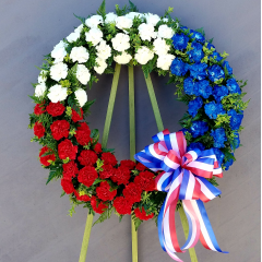 "This is a large 24"" wreath in patriotic tones to honor your family Hero. We are also able to insert a photo of your loved one or add a memorial banner through the center of the wreath to convey your sentiment."