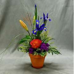 "When you want to brighten someone's day with a garden collection of vibrant flowers and a rustic handmade butterfly sculpture this is the perfect design. Approximately 16"" tall."