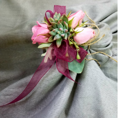 This wristlet is a combination of rustic charm with succulents and jute incorporated with the elegance of spray roses and ribbon. A unique upscale look that creates a one of a kind design for a wedding day or formal!
