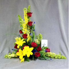 Table top, stylized urn display is a bright mix of seasonal flowers including red roses to convey your love. This design works nicely with either an urn or a photograph of your loved one. Best size for photo is framed 8x10 or 11x14.