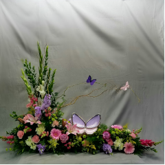 A magnificent floral display that captures the feel of a walk in the garden. This tranquil design features a plethora of soft feminine garden florals. Whimsical butterflies flutter above the urn taking flight to the heavens. This is a very special design that speaks from the heart. The Butterfly Urn is available at Greenlawn Mortuary in Bakersfield CA and is sold separately from the floral display it is featured in.