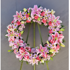 A Tasteful Design Of Stargazer Lilies, Lavender Daisies And Carnations In A Beautiful Mixed Wreath-A Touching Tribute.