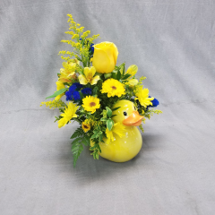 Cute As A Baby Duck, This Arrangement, In A Keepsake Container, Is Full Of Bright Yellow Flowers Including A Single Stem Yellow Rose, Alstromeria, Mums And Purple Statice.