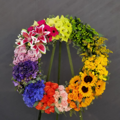 "A BREATH TAKING 24"" STANDING WREATH DESIGNED WITH ALL THE COLORS OF THE RAINBOW. PERFECT FOR THE PERSON WHO LOVED LIFE AND ALL IT'S MANY COLORS!"