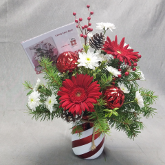 Feel the spirit of the season! This is bouquet is the perfect holiday gift for that hard to buy for person. It is a festive candy stripe jar container filled will fresh christmas greens and red and white seasonal flowers PLUS it comes with a box of peppermint bark candy and also includes a Better Homes and Gardens recipe to make your own peppermint bark candy! Call early this show stopper is going to sell out fast!