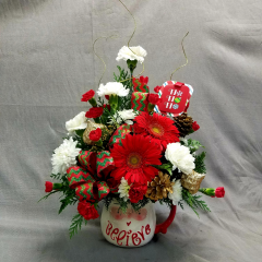 "Put a smile on the face of someone special for the holidays with Log Cabin's Ho Ho Ho Mug arrangement! A quality painted ceramic mug filled to the brim with seasonal flowers and fresh Christmas greens! This is a one sided arrangement that is approximately 18"" tall and 15"" wide."