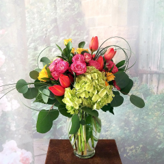 """This is a fresh, modern take on the traditional mixed spring arrangement bursting with the glorious colors of Spring! Arrangement is approximately 18"""" tall and wide and designed in an all around style suitable for a table centerpiece or desk."""