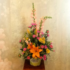 This is a large arrangement bursting with all the colors of Spring. Standing approximately 30 inches tall and 22' wide it makes a nice presence for any occasion! It would look amazing on your Easter Table buffett too!