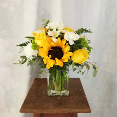 "Three gorgeous sunflowers captivate this bouquet, along with green button poms, yellow roses and ivory blossoms. Approx. 13"" H x 12"" W"