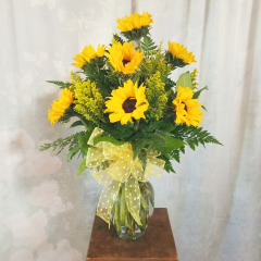 "Surprise Someone Special with a Blast of Brilliant Sunflowers!   Filled with Sunflowers and Solidago, this gorgeous arrangement is accented with a yellow bow.  (Container may very)...Approx 24"" Tall a"