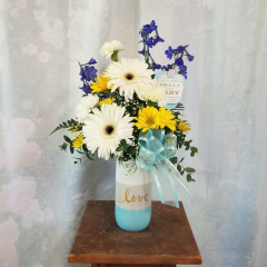 "A sweet arrg for a new baby boy in gerbera daisies, delphinium, daisies in a cute striped keepsake container that says 'love' and sweet baby boy tag. Approx 20""H x 12""W"
