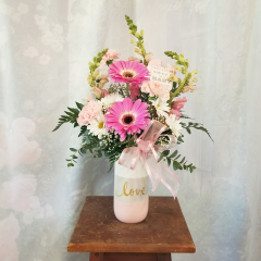"""A sweet arrg for a new baby girl in gerbera daisies, snaps, daisies, and carnations in a cute striped keepsake container that says 'love' and sweet baby girl tag. Approx 20""""H x 12""""W"""