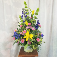 This is a large arrangement bursting with all the colors of Spring. Standing approximately 30 inches tall and 18' wide it makes a nice presence for any occasion!