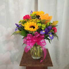 "Summer fresh blooms Of Hot Pink Carnations, Iris, Sunflowers, Asiatic Lilies, Kermits, and Filler to make the perfect Summer bouquet! **Flowers subject to change depending on availability of season** As shown is approx. 17""H x 14"" W"