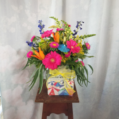 """A bright & vibrant mixed bouquet of gerbs, lilies, asters, delphinium, snaps and filler in a vase, comes with a festive summer theme 1/2 lb box of See's chocolates. One sided arrg. approx 20""""H x 15""""W. ***Flowers may be subject to change due to availability***"""
