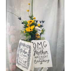 """Fun summer arrangement in a decorative wire container with sunflowers, craspedia, thistle. Can add a tea towel for an additional $12.95. approx 21"""" h x 8""""w **Sayings on towels will vary**"""