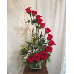 "This arrangement of 1 dozen roses is for the person who appreciates the unusual. It is not only beautiful but it makes a statement and creates conversation every time it is delivered! **If desired can change rose color to: Red, White, Yellow, Pink or Cherry Brandy** Approx. 25"" high"
