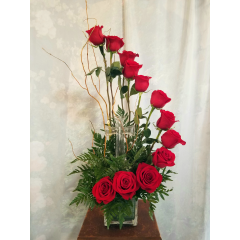 Dozen Roses in a unique spiral design in a cube. Comes with a glass keepsake cross in the center of arrangement as a remembrance. **colors of roses can vary in red, white, pink, cherry brandy or yellow**