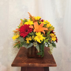 "A cute little fall bouquet in a cube which comes in fall colors of green, red or orange. A nice mix of gerbs, sunflowers, lilies, daisies, alstro and solidago. **Flowers may vary upon availabilty** Approx. 12"" x 12"""