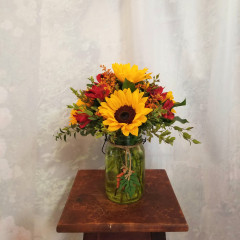 "Cute little bouquet in a mason jar with decorative leaves around the top of vase with a nice fall bouquet of sunflowers, alstro and solidago. Approx. 13""h x 10""w"