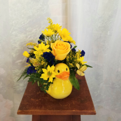Cute as a baby duck, This arrangement, in a keepsake container, is full of bright yellow flowers including a single stem yellow rose, alstromeria, daisies and blue statice.