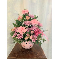 "A well crafted ceramic keepsake container overflowing with pink and lavender flowers that celebrate the birth of a very special little someone. Also available in blue tones and blue crafted ceramic for a precious baby boy too! approximately 15"" tall. Add a mylar balloon to finish the look!"