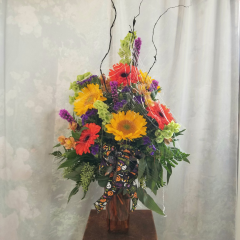 "A festive bouquet in an orange vase with gerbera daisies, sunflowers, alstromeria, and statice with curly willow covered in spiderwebs!! Approx. 29""H x 17""W **This is a one sided arrangement**"
