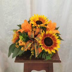 "Cute little fall centerpiece that would look great on a dining room table, end table or just to brighten someones day!! Fall tones in sunflowers, spider mums, asiatic lilies and wax flower. Approx. 10H x 13""w"