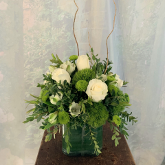 This contemporary clear cube arrangement holds an array Of roses, alstromeria, green kermits and hypericum berry.