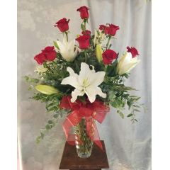 "All her favorites! Dozen long-stemmed Red Roses and 6 Fragrant White Lilies. A romantic gift she will treasure! This arrangement is designed in an upgraded vase and stands approximately 33""H x 25""W!"