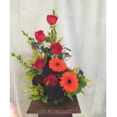 "A tasteful design of red roses, gerbera daisies and other colorful flowers designed in a lovely metal dish, a great way to say ""job well done'! **Flowers and container may vary depending upon availability** Approx 21""H x 14""W"