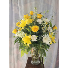 "A beautiful combination of yellow roses & lilies arranged with stock,delphinium and spider mums. This is a welcome gift for the family. Approx. 32"" tall"