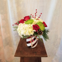 """A festive keepsake container that looks like a peppermint stick stripes with hydrangea, roses, spiders, pine cones and silk red berries with Chirstmas greens. Approx 14""""H x 12""""W **flowers may be subject to change**"""