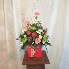 """Cute arrangement in a ceramic container that looks like a present with peppermint carnations, mini carnations, spiders, white poms, ornaments, pine cone, ting ting. Approx 19""""H x 14""""W **flowers may be subject to change**"""