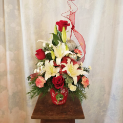 """A festive container with a jingle bell to brighten the holidays with roses, lilies, carnations, ornaments and ribbon treatment. Approx 19""""H x 13""""W. **Flowers may be subject to change**"""