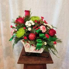 """Cute keepsake wooden sleigh with roses, spider mums, button poms, carnations, mini carns, hypericum berries with ribbon treatment and ornaments. Approx. 15"""" H x 17"""" L. **Flowers may be subject to change**"""