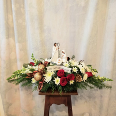 """Keepsake nativity centered in middle of centerpiece with roses, spiders, snaps, cushion poms, ribbon treatment, ornaments. Approx 13""""H x 32""""L. **Flowers may be subject to change**"""