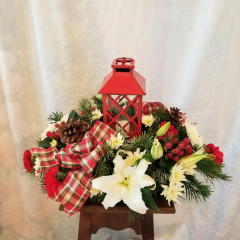 """Fun festive lantern centerpiece that will brighten any table or coffee table with lilies, red carns, cushion poms, hypericum berries, natural pine cone and ribbon  treatment. Approx 13""""H x 20""""L. **Flowers may be subject to change**"""